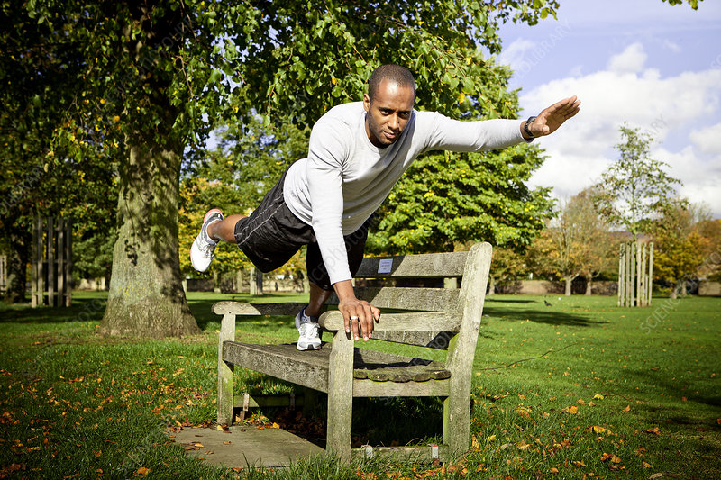 Man in plank position on park bench