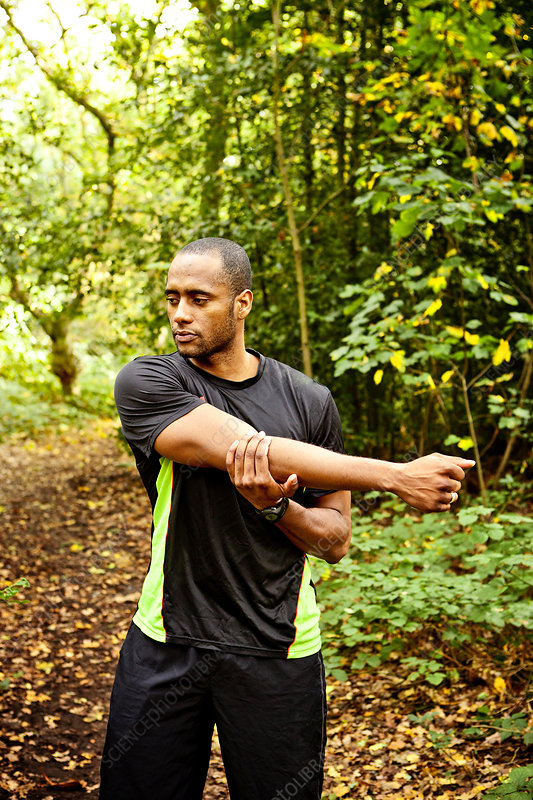 Man stretching arms in woods
