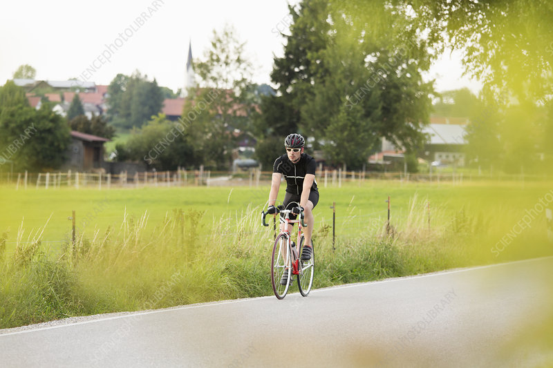 Mature male cycling on country road
