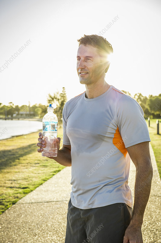 Mature male runner holding water bottle