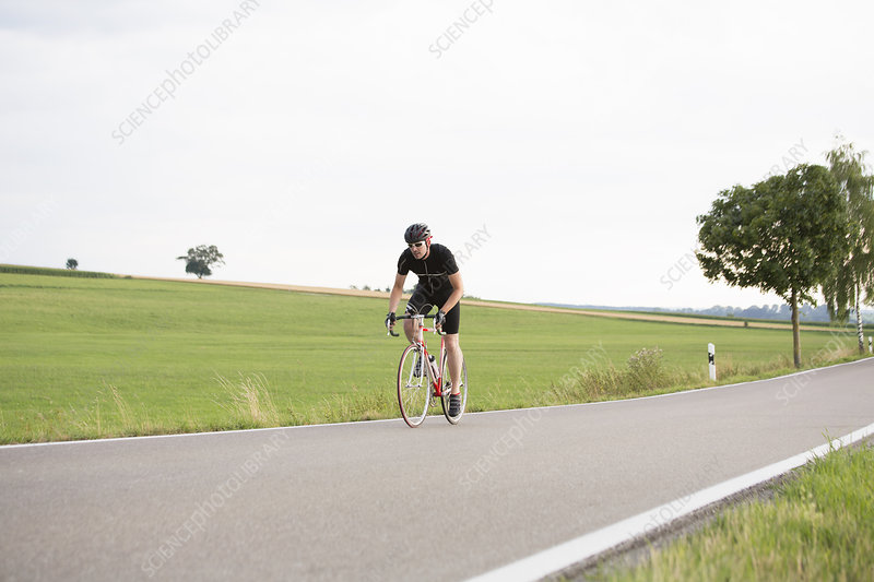 Mature man cycling along country road