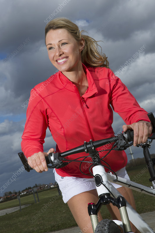 Mid adult woman on bicycle