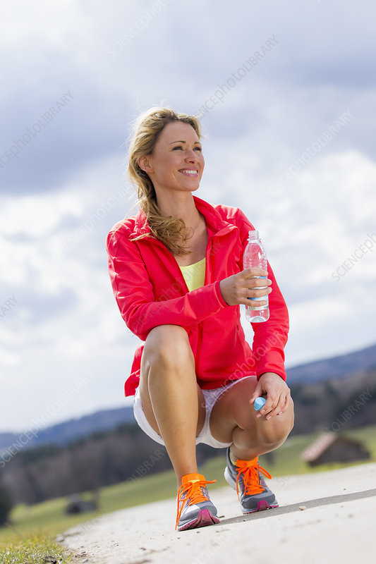 Mid adult woman with bottle of water