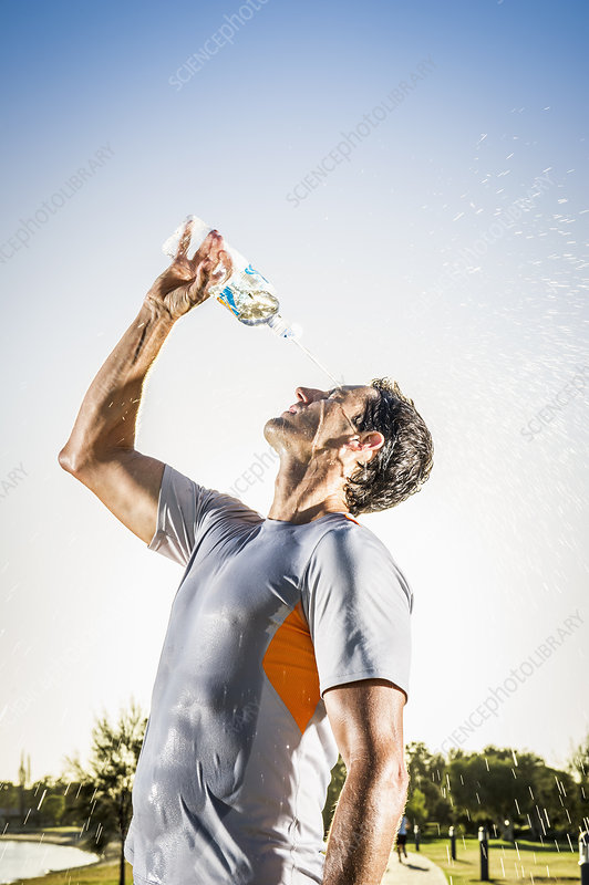 Runner pouring water bottle over his face