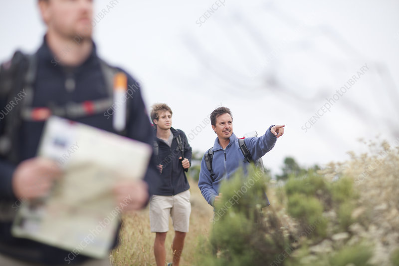 Three male hikers with backpacks and map