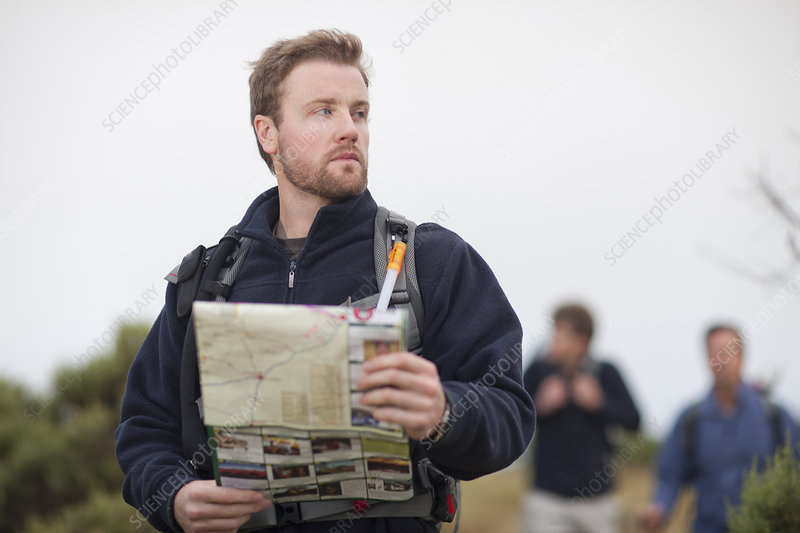 Three men hiking with backpacks and map