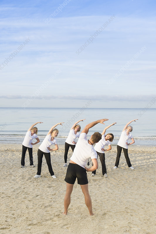 Trainer and women exercising on beach