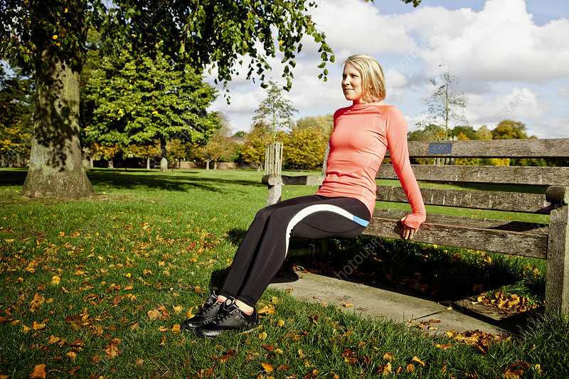 Woman exercising on park bench