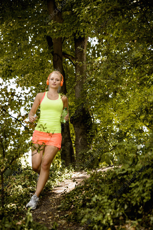 Woman in headphones running in woods