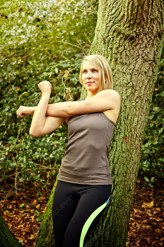 Woman stretching arms in woods