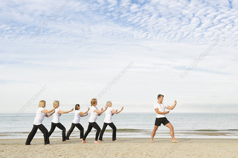 Women and trainer exercising on beach