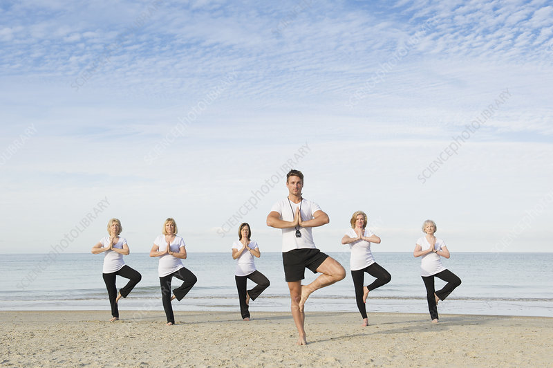 Women and trainer practicing tree pose
