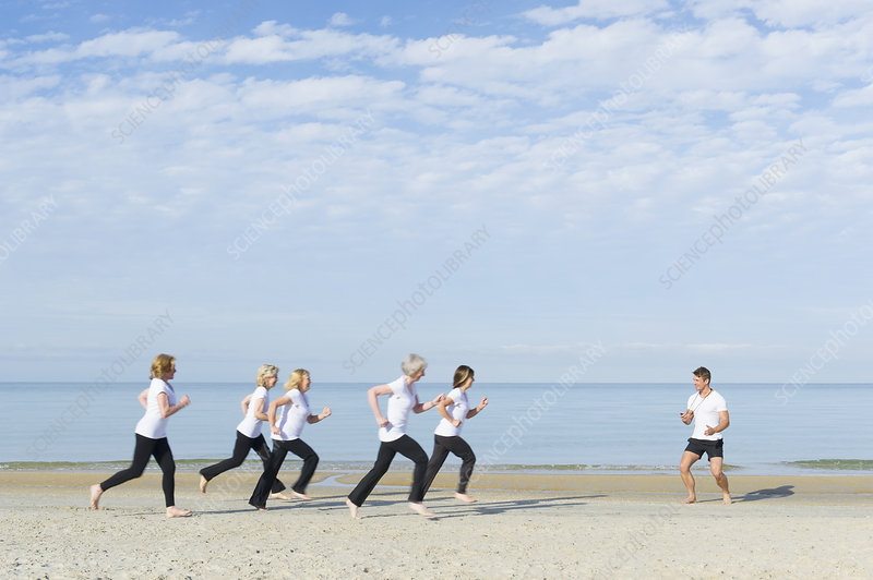 Women and trainer running on beach