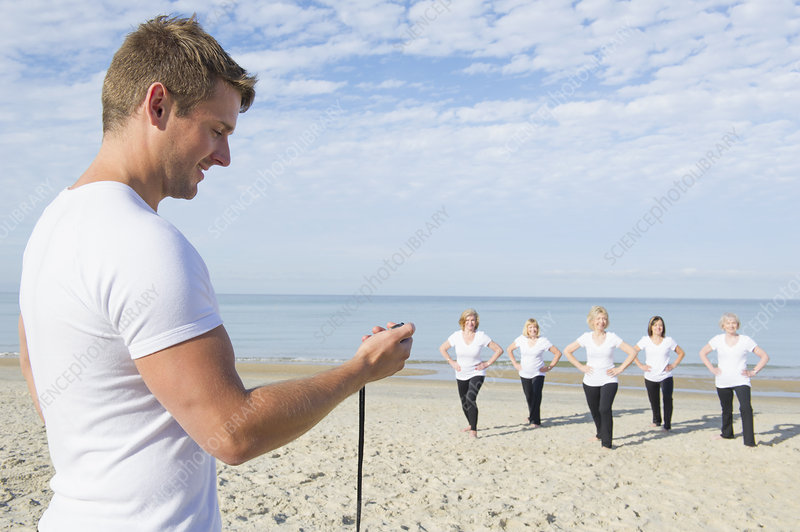 Women having fitness class on beach