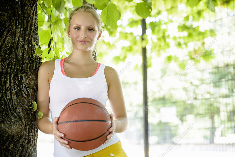 Young female basketball player in park