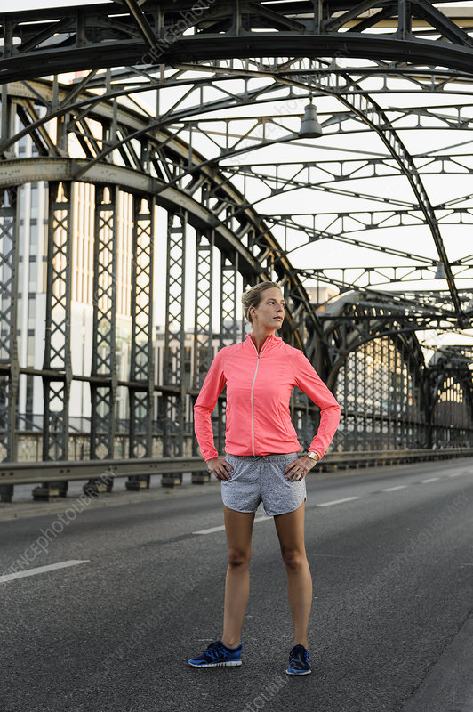Young female runner exercising on bridge