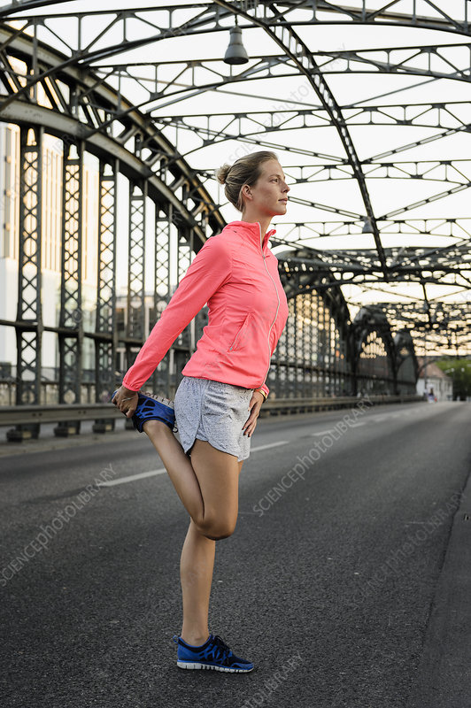 Young female runner stretching on bridge