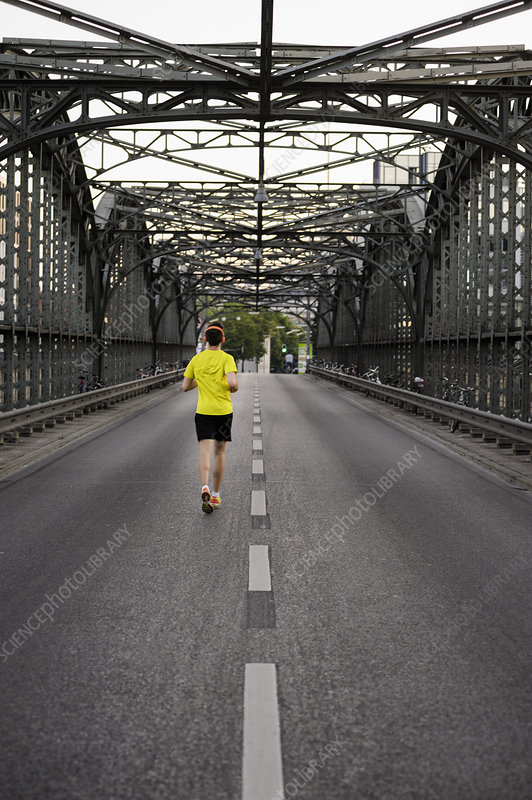 Young male athlete running over bridge