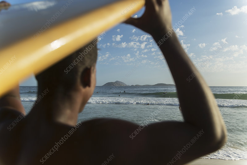 Young man carrying surfboard, Brazil