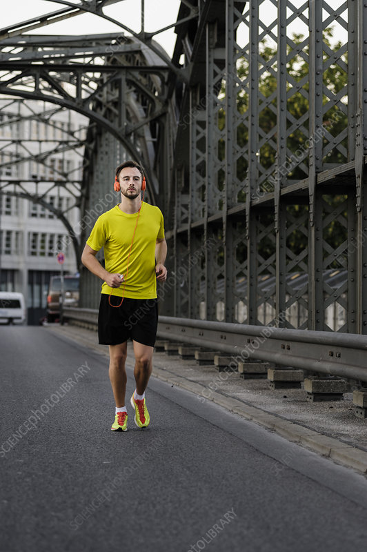 Young man running on bridge
