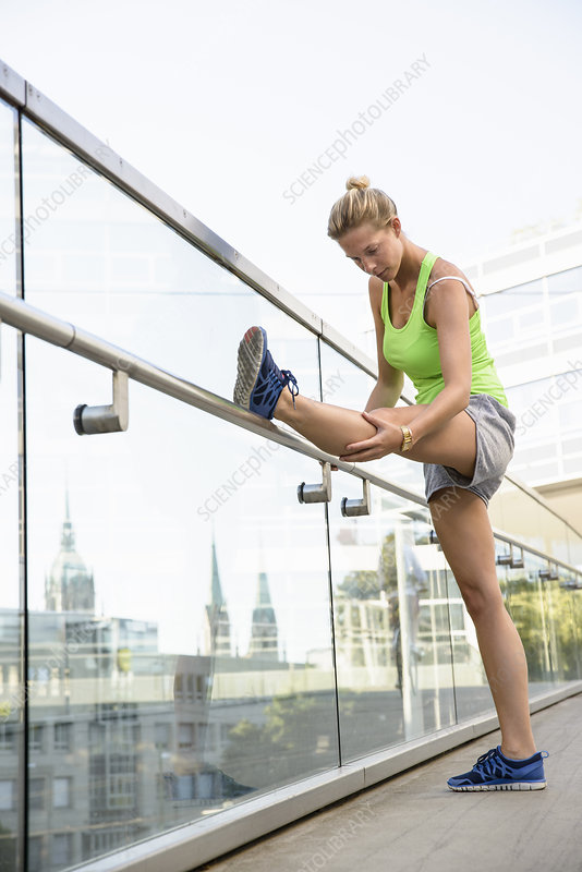 Young woman stretching leg