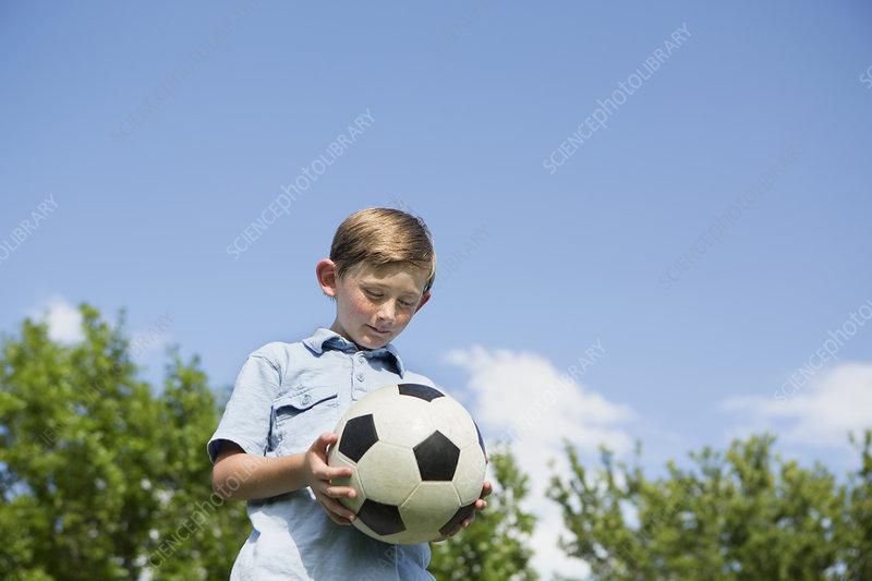 A young boy holding a soccer ball