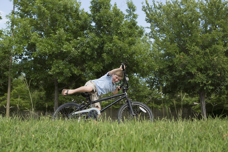 A young boy falling off his bicycle
