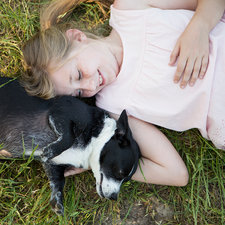 A girl hugging a black and white dog