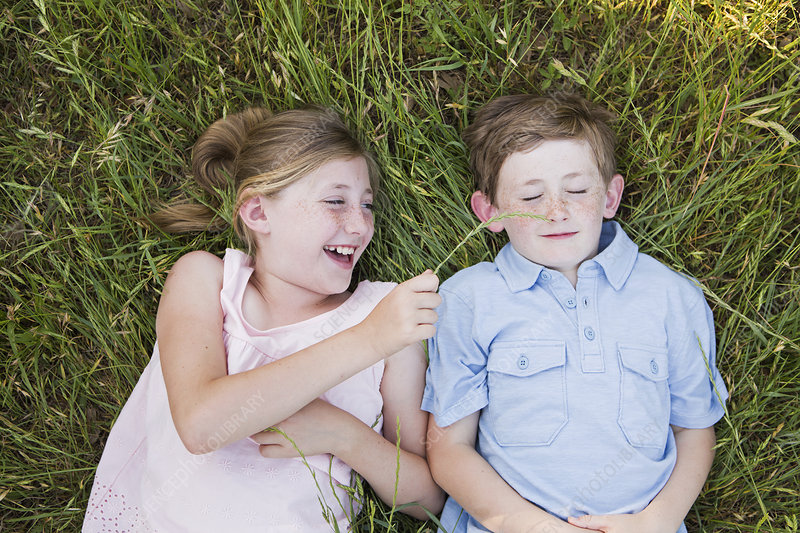 Brother and sister lying on the grass