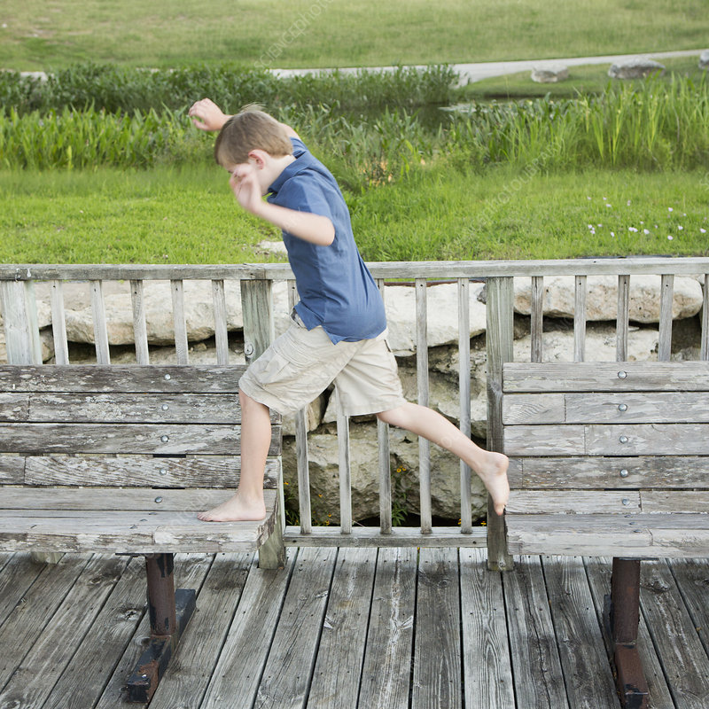 A boy leaping from one bench to another