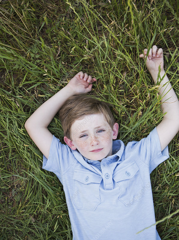 A boy in a blue shirt lying on his back