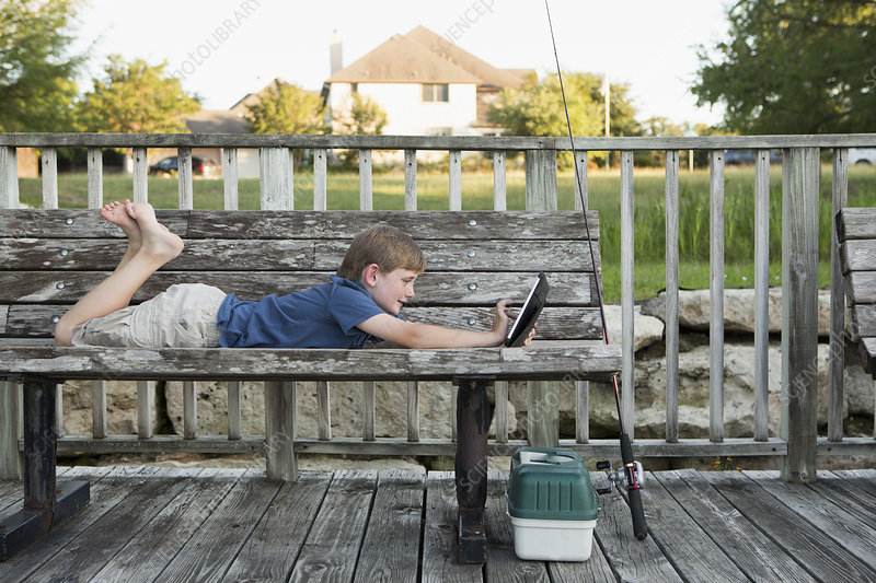A young boy with digital tablet outdoors