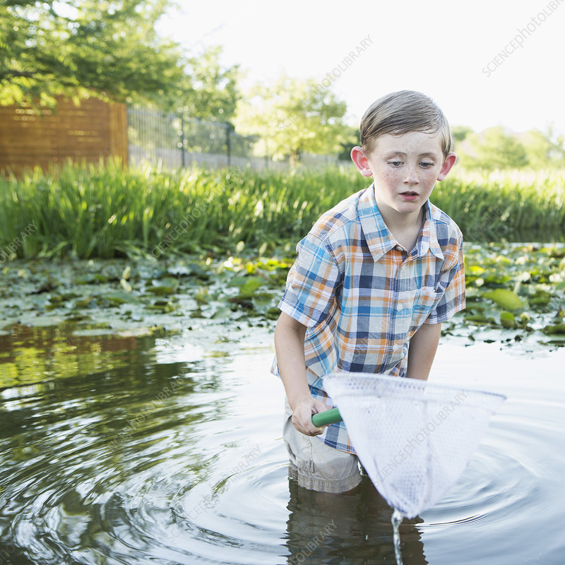 A young boy standing thigh deep in water