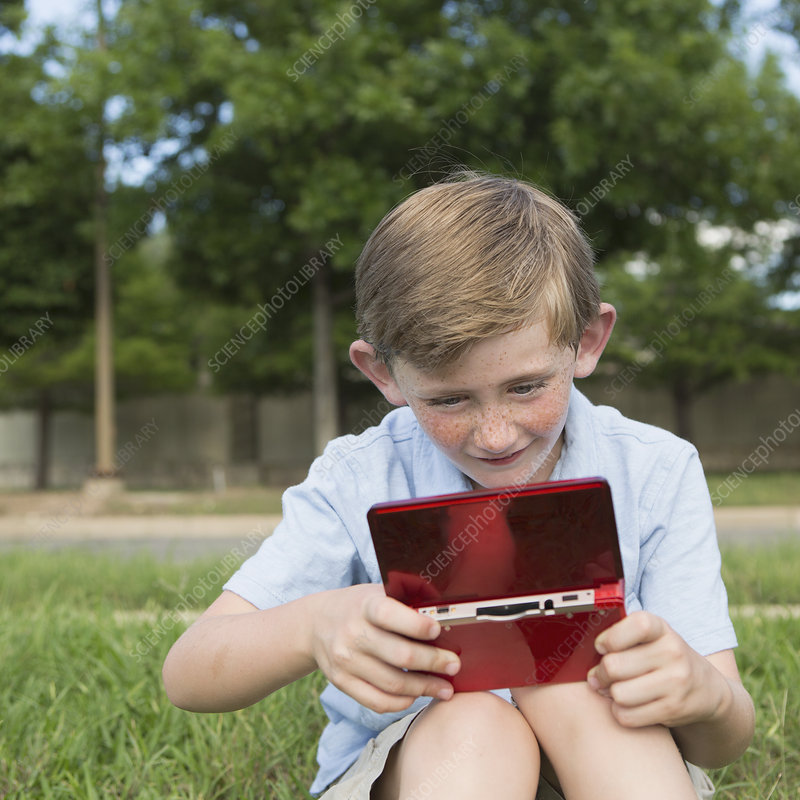 A young boy using electronic game device