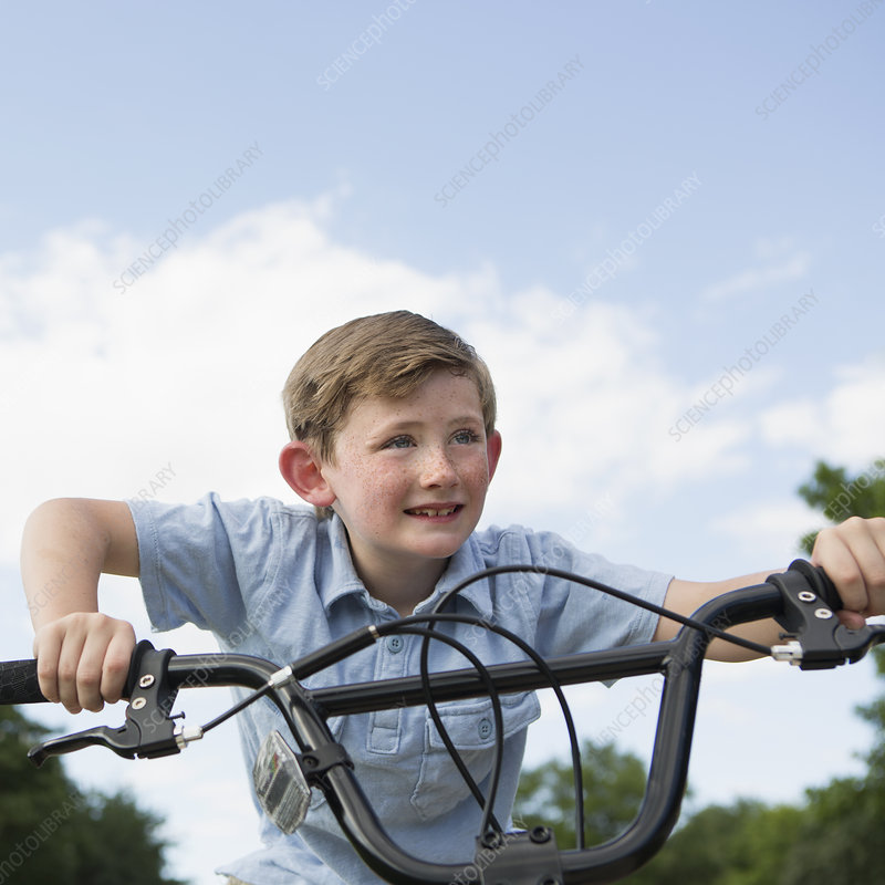 Boy leaning over handlebars of bicycle