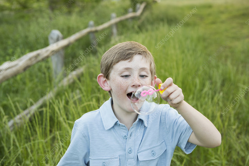 A boy in a blue shirt, blowing bubbles