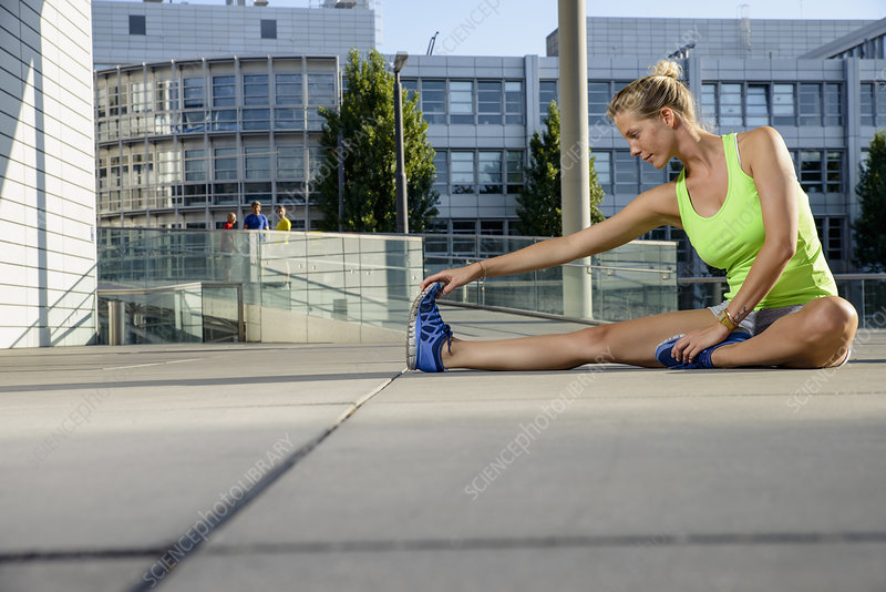 Female runner stretching on city rooftop
