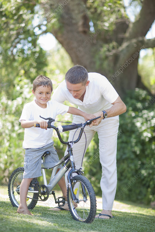 Father guiding son to cycle