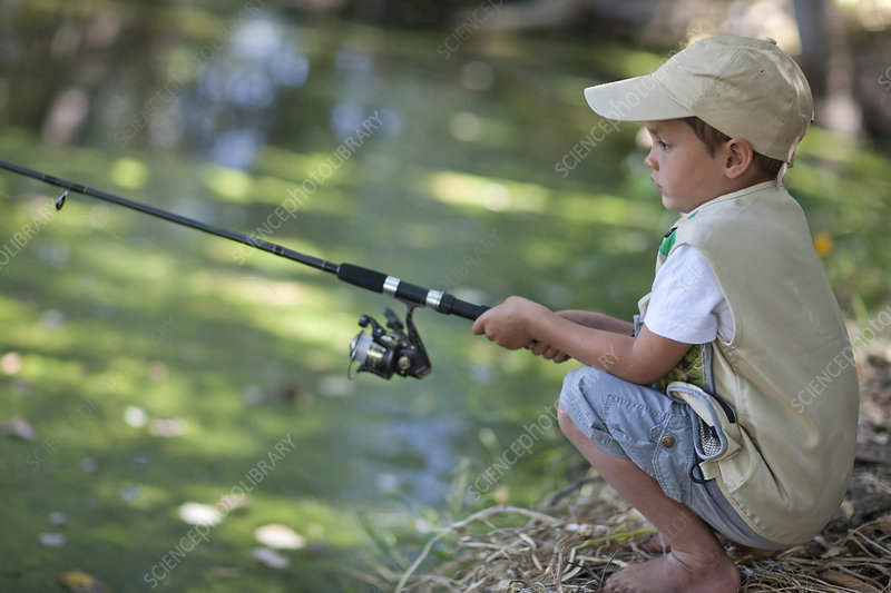 Boy fishing by stream