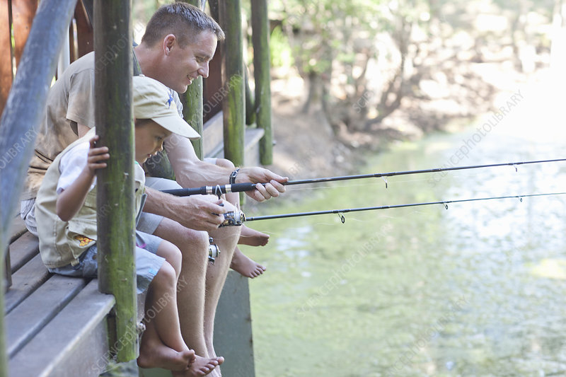 Father and sons fishing by stream