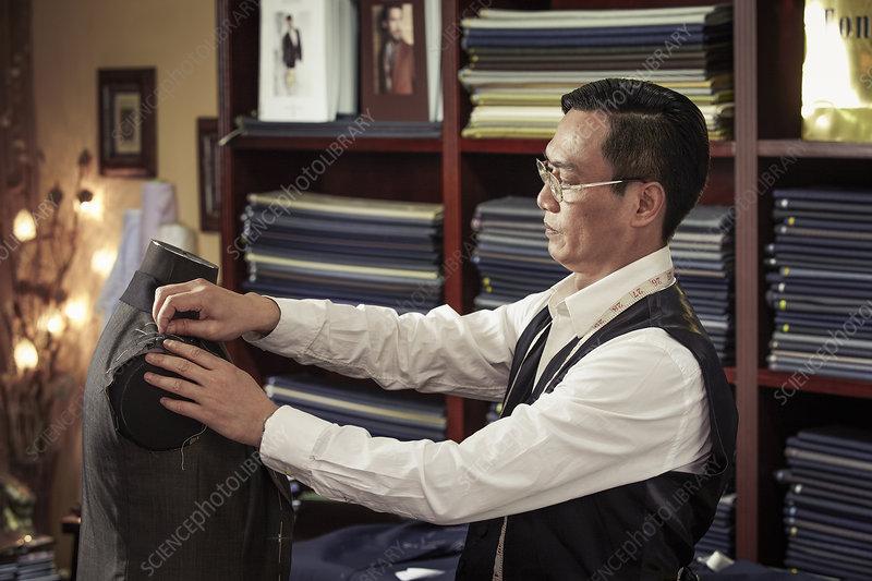 Tailor pinning garment on tailors dummy