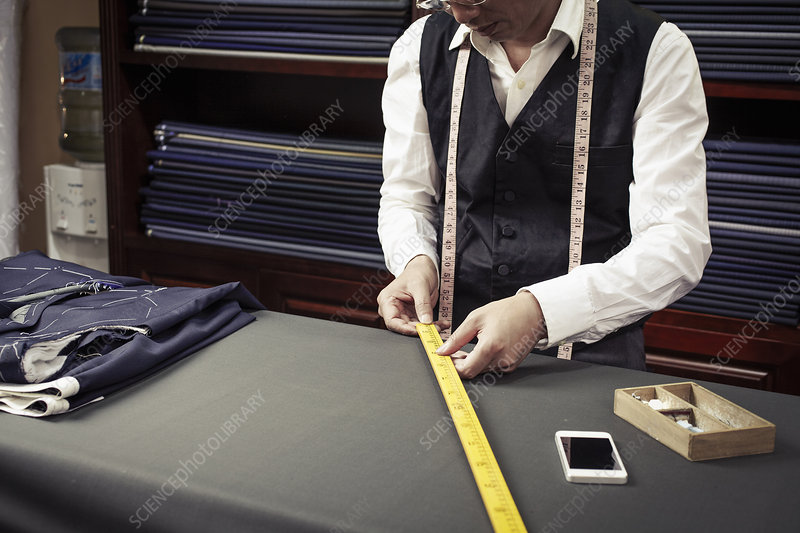 Tailor taking measurements from ruler