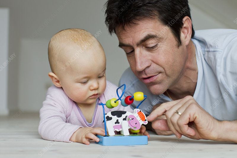 Man and baby daughter playing with toy