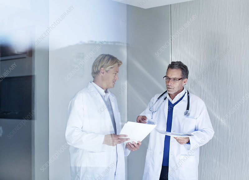 Two male doctors discussing medical notes