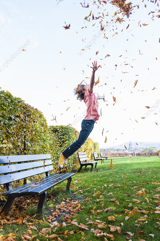 Boy jumping scattering leaves into air