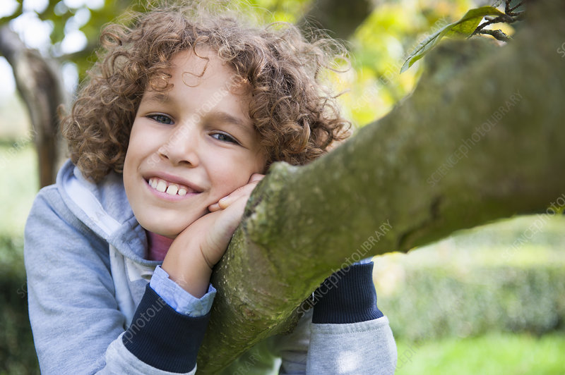 Boy lying on tree
