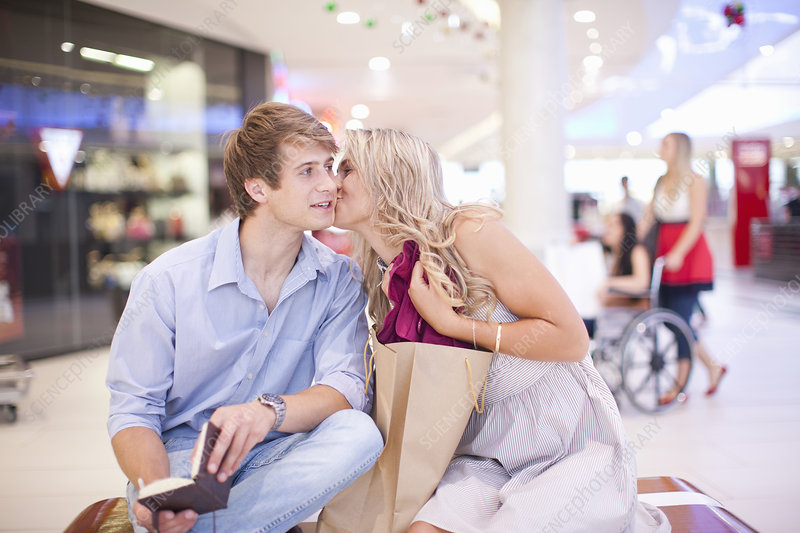 Young woman kissing man's cheek at mall