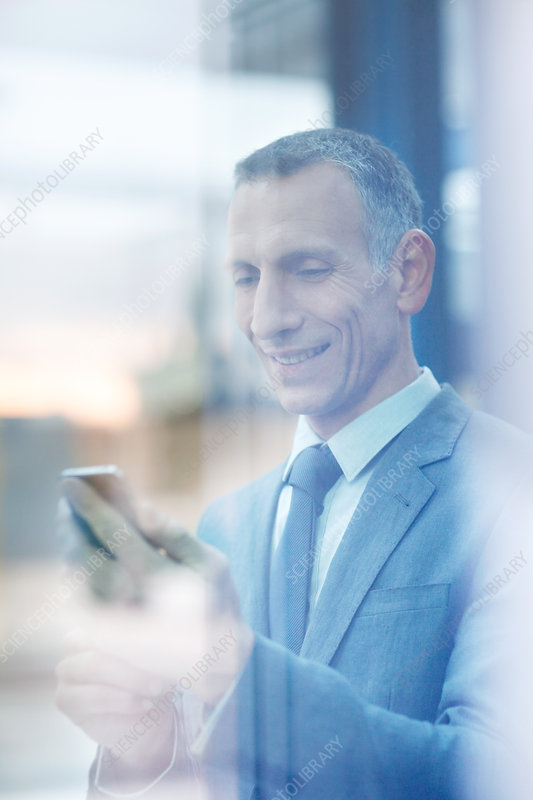 Businessman reading texts on smartphone