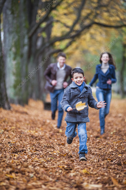 Family running through autumn leaves