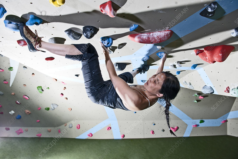 Woman bouldering on climbing wall